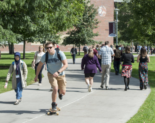 Male student on longboard, University of Montana