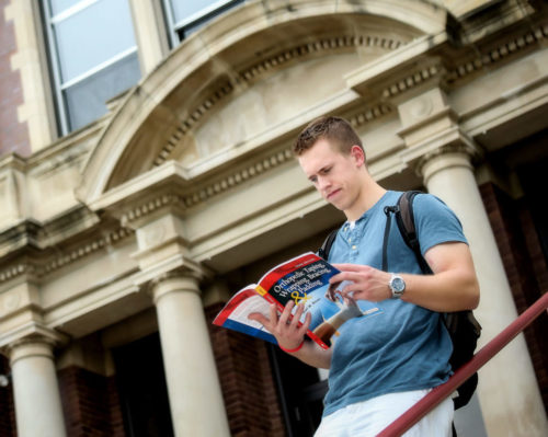 Student reading Orthopedic textbook at Minot State University