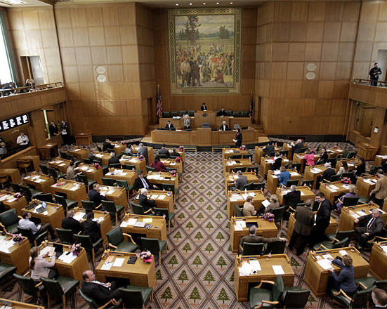 Oregon representatives gather on the House floor as Oregon's 77th legislative session gets under way in Salem, Ore., Monday, Feb. 4, 2013